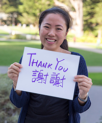 "A student holds a ""thank you"" sign"